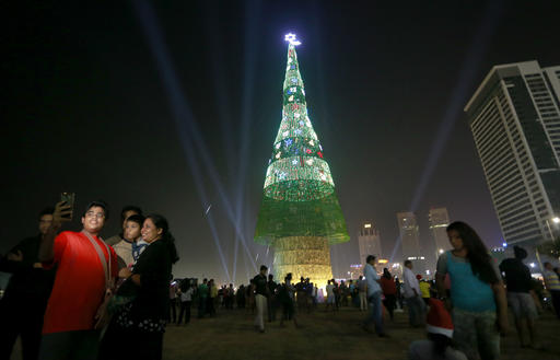 A family standing near an enormous artificial Christmas in Colombo, Sri Lanka, Saturday, Dec. 24.