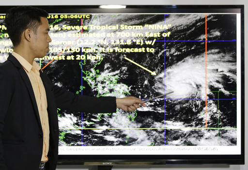 Weather specialist Benison Estareja shows the track of Tropical Storm Nock-Ten during a press conference in Quezon city, north of Manila, Philippines