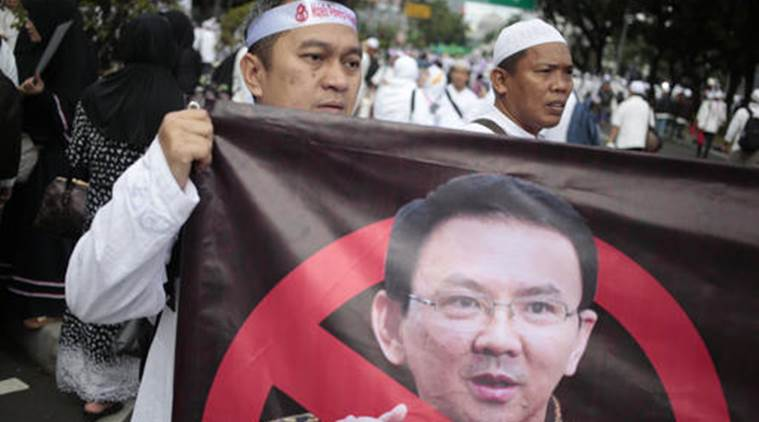 一名穆斯林男子走上雅加達街頭,抗議鍾萬學褻瀆《可蘭經》。(圖片來源:Associated Press)