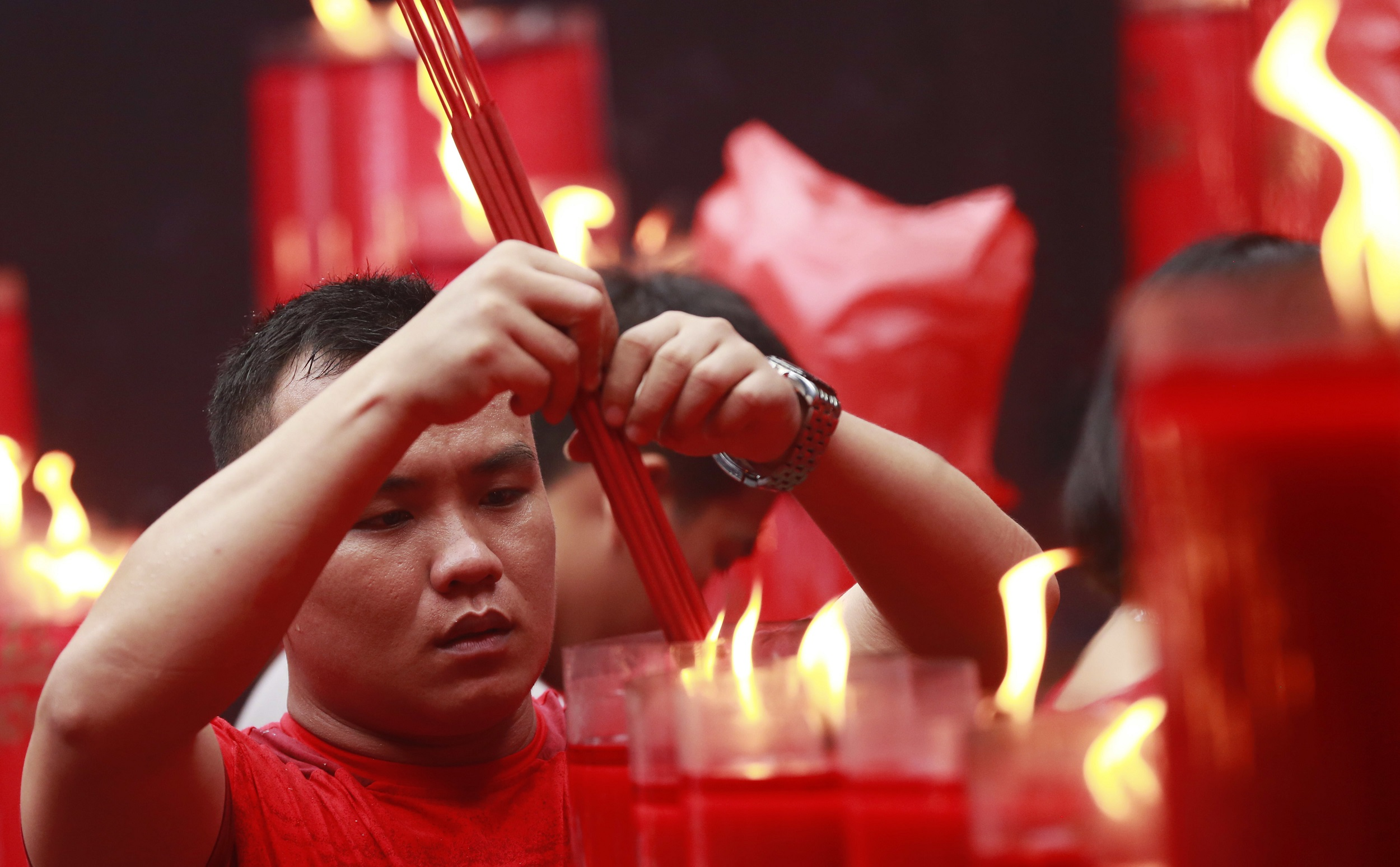 A man lighting incense during Lunar New Year