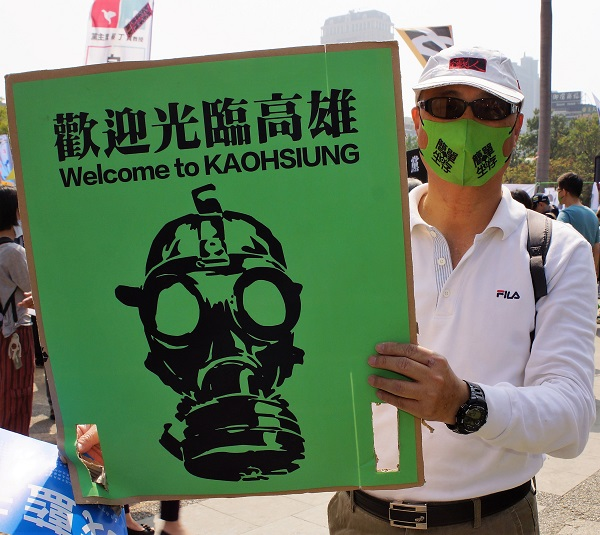 """A protester wearing a face mask holds up a sign """"Welcome to Kaohsiung"""" featuring a person with a gas mask."""