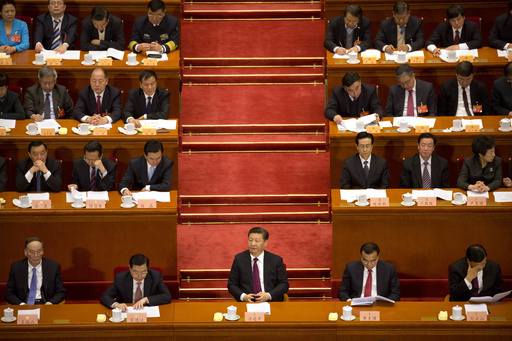 Chinese President Xi Jinping, center, listens to a speech during the opening session of the Chinese People's Political Consultative Conference in Beij...