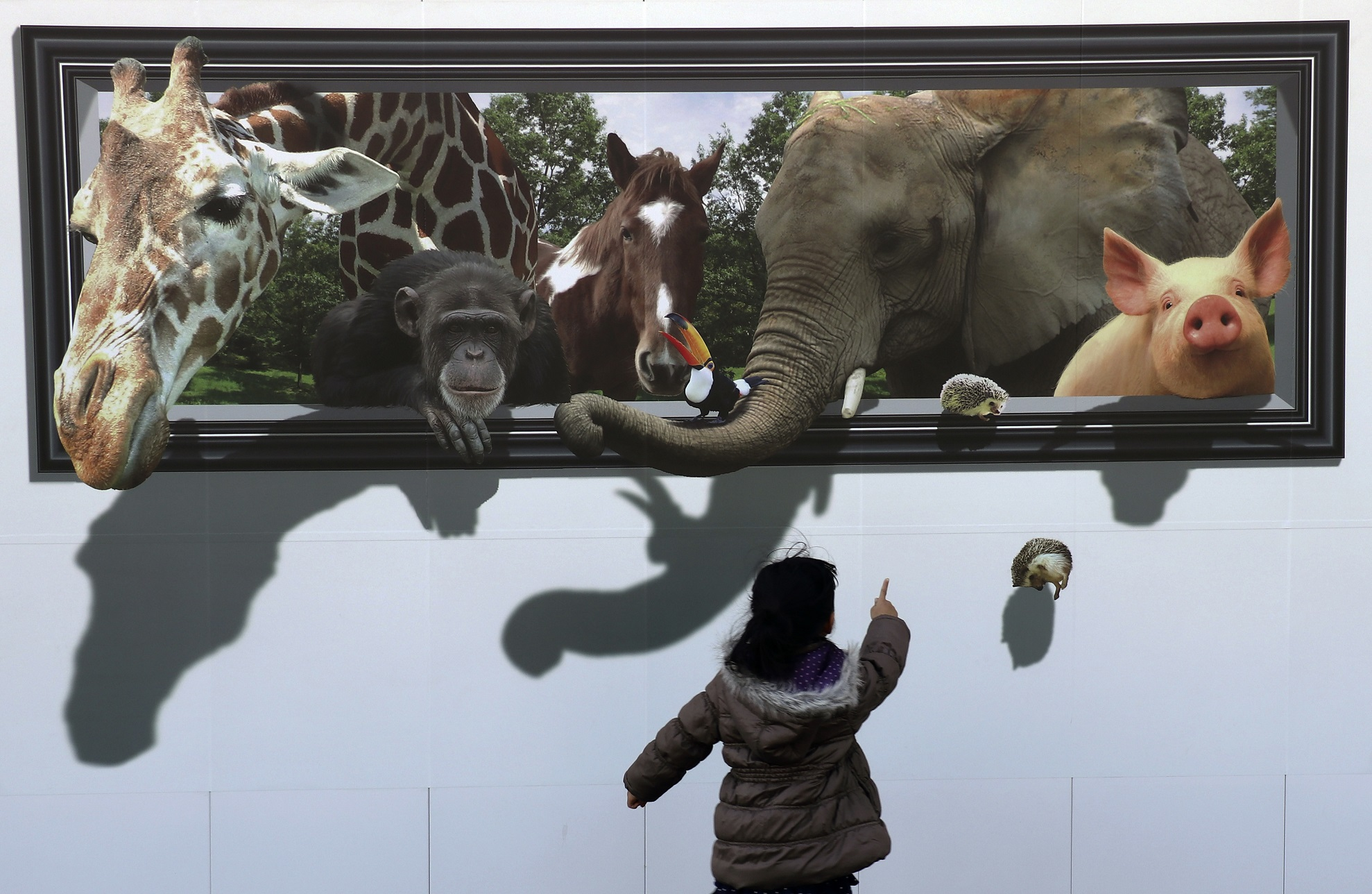 A girl reacts to a 3D drawing of animals on the safety wall at a construction site of the archery venue for the Tokyo 2020 Summer Olympics in Tokyo.