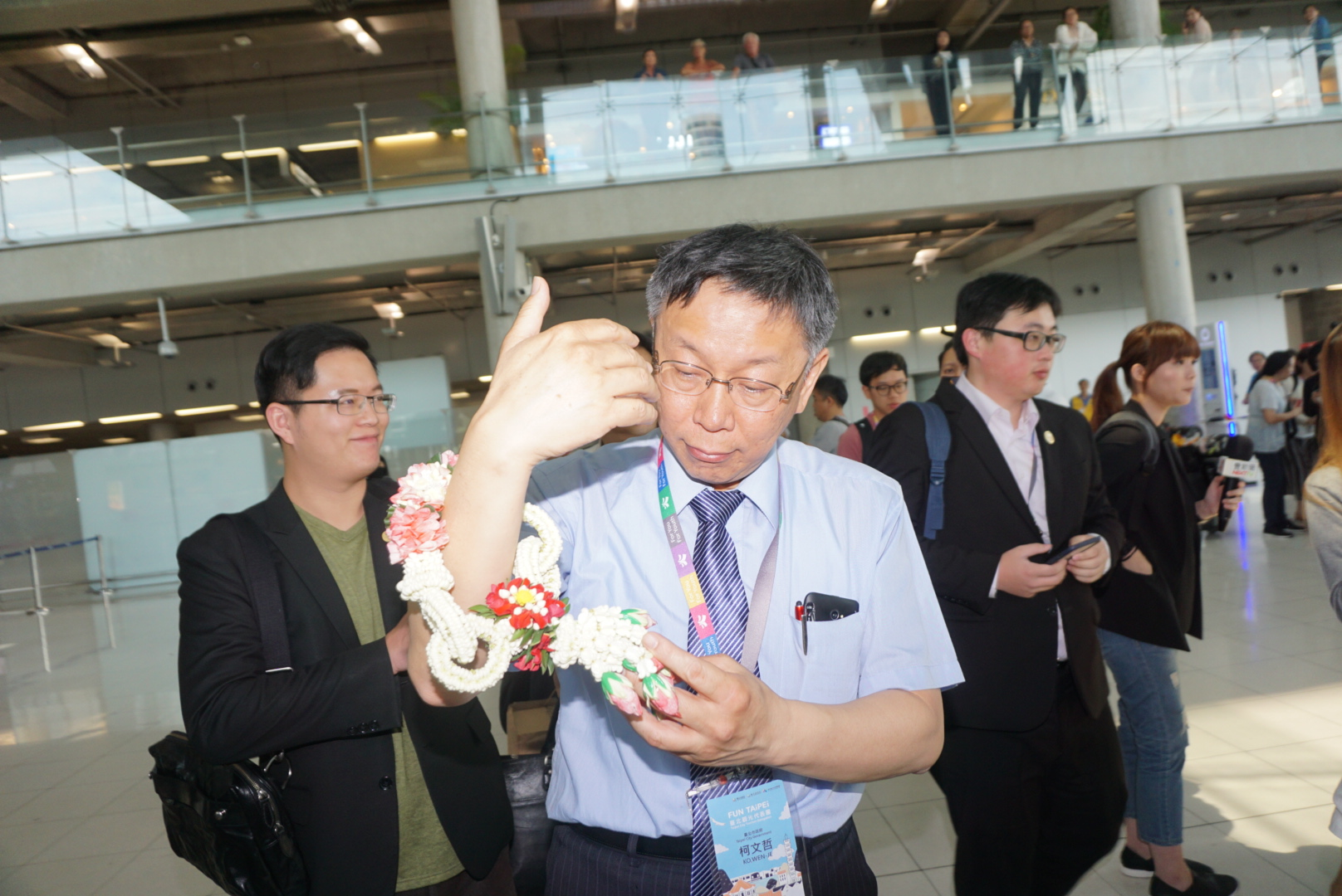 Mayor Ko Wen-je receives flowers as he arrives in Bangkok