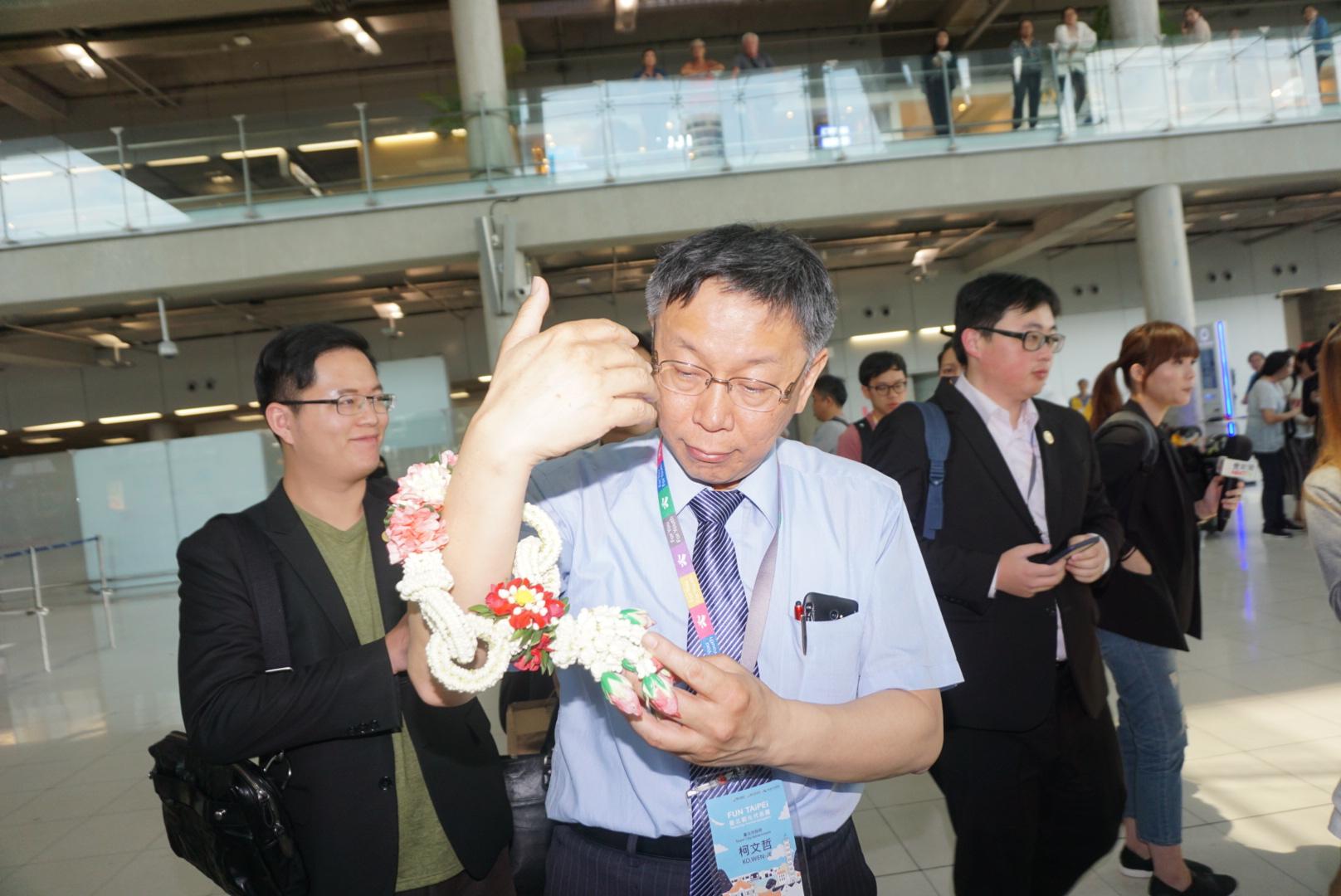 Mayor Ko Wen-je receives flowers as he arrives in Bangkok
