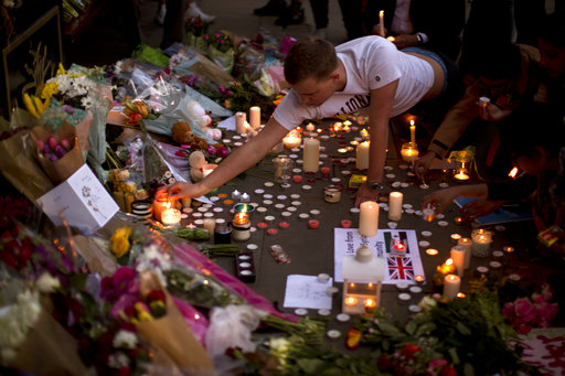 A man lights candles after a vigil in Albert Square, Manchester, England