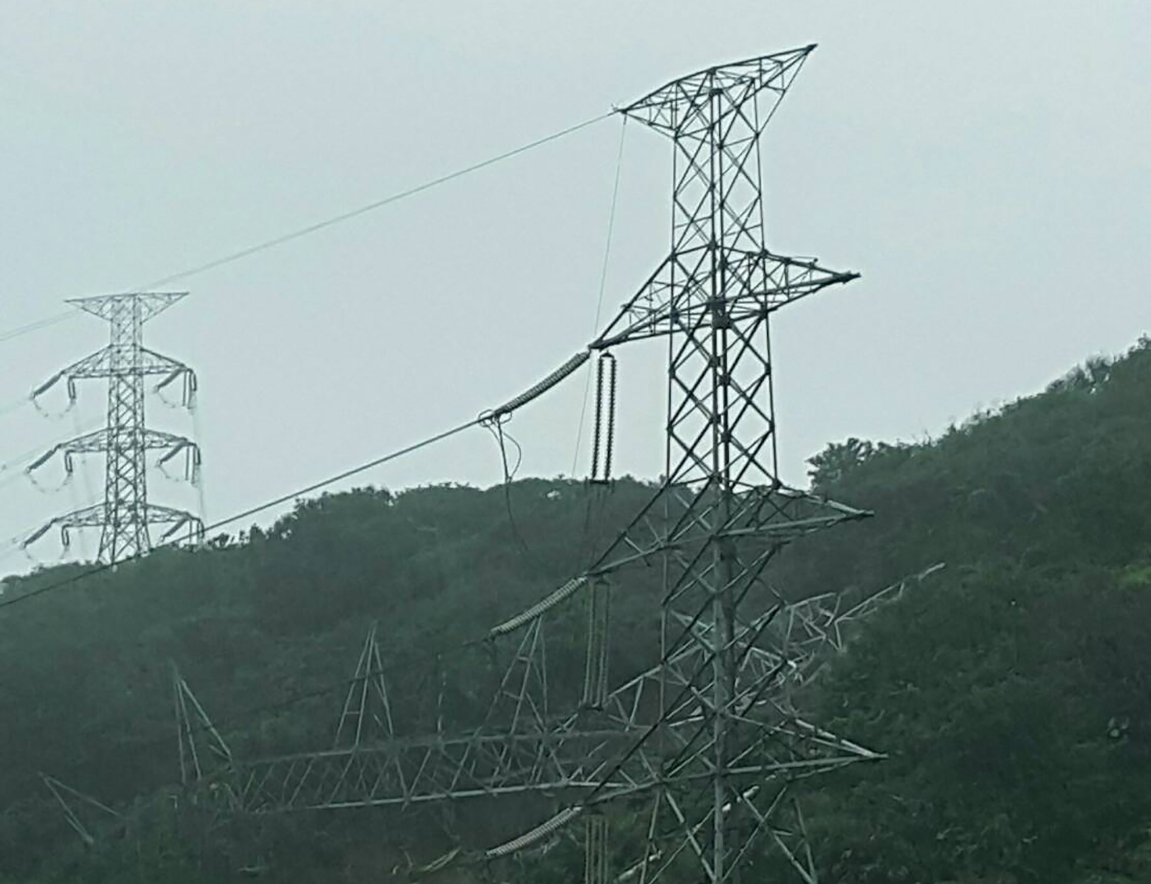 Toppled power tower strewn on hillside.