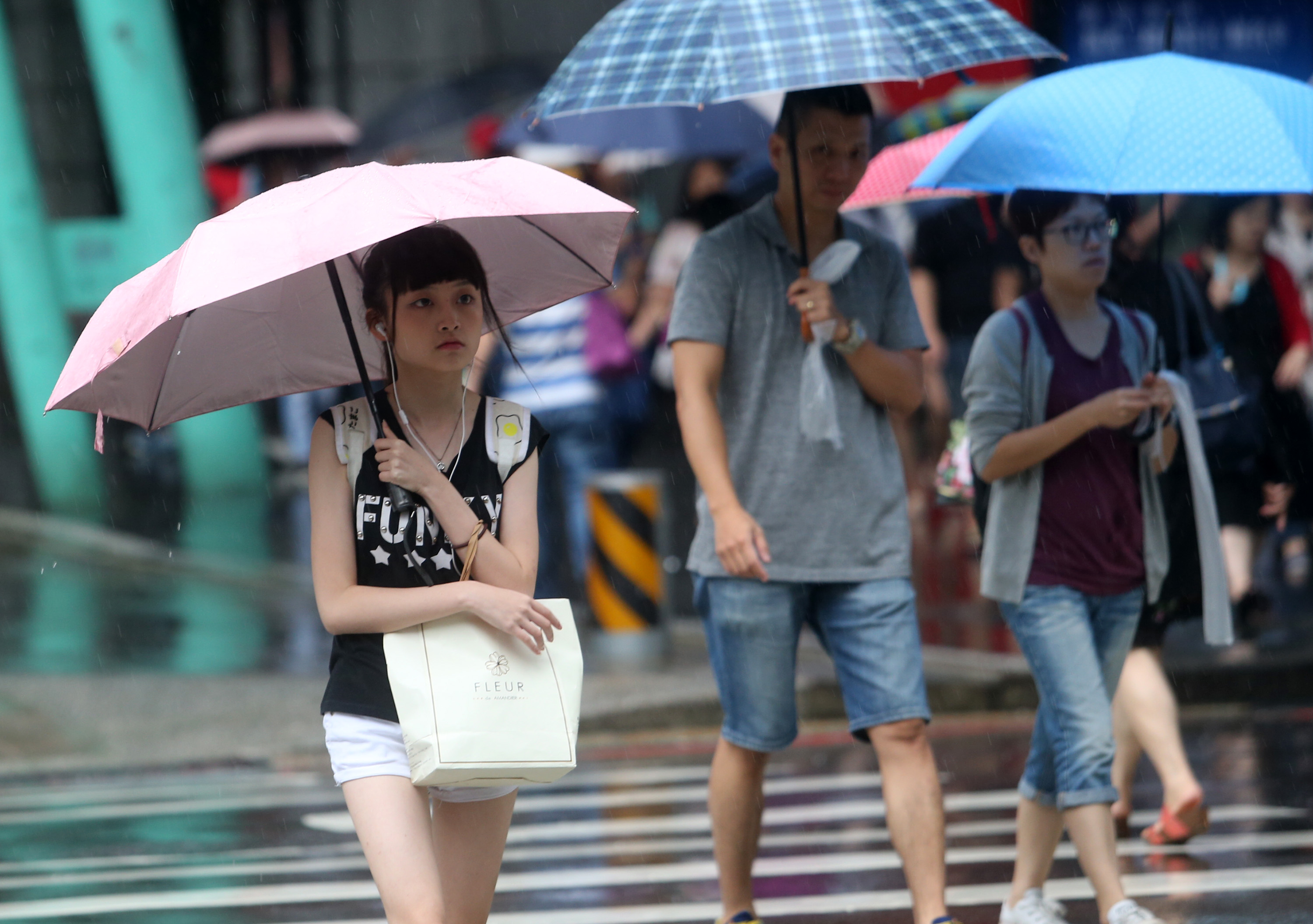 A girl crosses a road in Xinyi District of Taipei on a rainy day.
