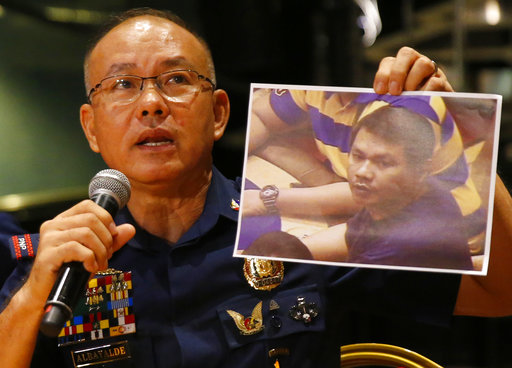 Police Gen. Oscar Albayalde holds a copy of an image of a gunman who stormed the Resorts World Manila complex .
