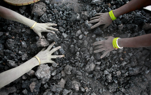 Indian women use bare hands to pick reusable pieces from heaps of used coal discarded by a carbon factory in Gauhati, India.