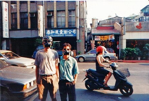 Author with friend wearing gas masks in Taipei in 1997.
