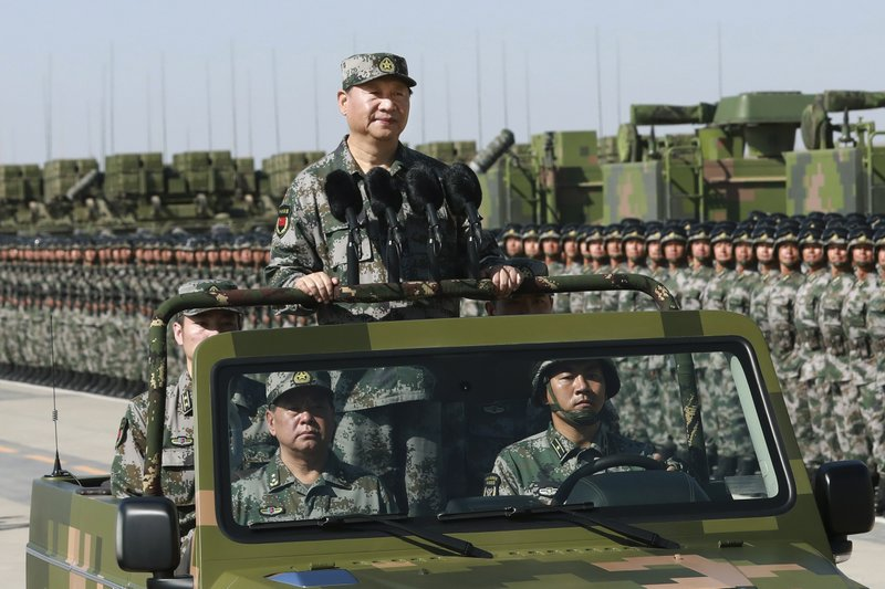 Chinese President Xi Jinping stands on a military jeep as he inspects troops of the People's Liberation Army during a military parade to commemorate t...