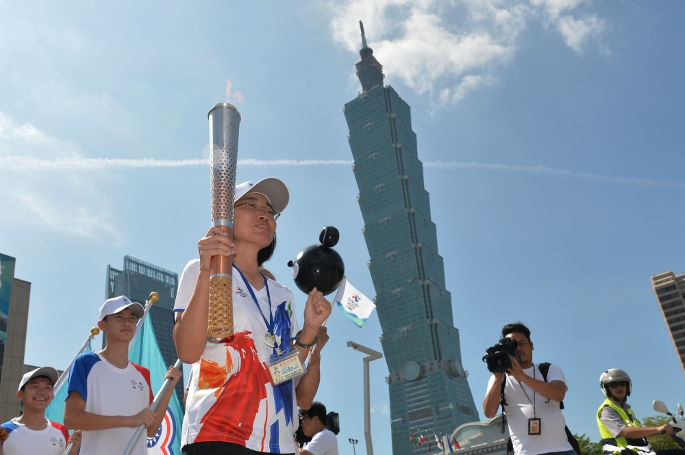 Xinyi District leader Yu Chu-ping carries torch near Taipei 101.