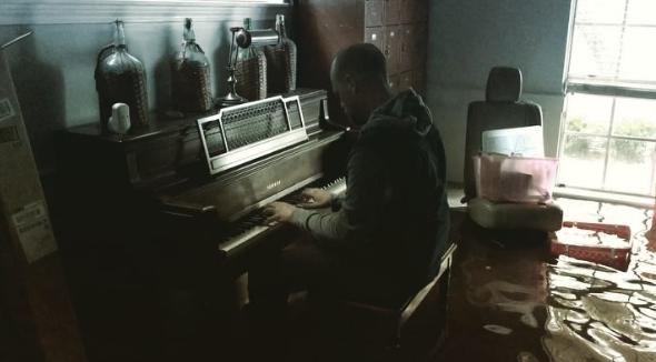 一名休士頓南部居民Aric Harding卻在洪災過後回到家中,彈起鋼琴苦中作樂,並以樂觀心態接受大自然帶來的一切。(圖片來源:取自Har