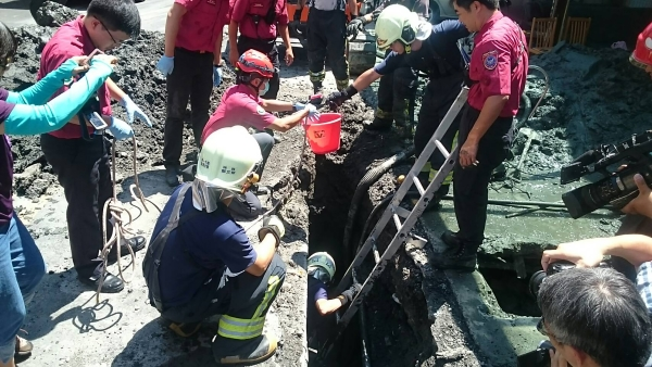 Rescue personnel try to retrieve man trapped in sewage ditch.