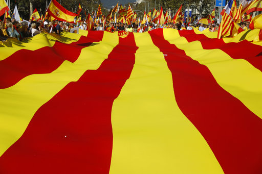 Nationalist activists protest with a giant Catalan flag during a mass rally against Catalonia's declaration of independence, in Barcelona, Spain, Sunday, Oct. 29, 2017.