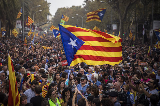 """People wave """"estelada"""" or pro independence flags in Barcelona, Spain."""