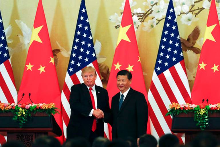 U.S. President Donald Trump shakes hands with Chinese leader Xi Jinping.