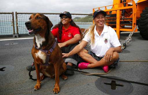 Jennifer Appel, right, and Tasha Fuiava sit with dogs on deck of USS Ashland.