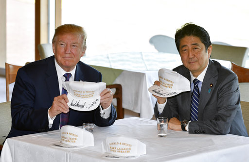 """Trump and Abe pose with hats reading """"Donald and Shinzo, Make Alliance Even Greater."""""""
