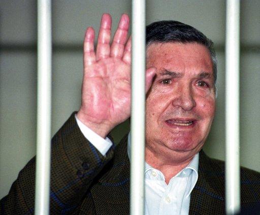 惡名昭彰的義大利黑手黨教父里納在1993年4月29日一場法院審判中向鐵欄杆外的記者揮手(圖片來源:美聯社檔案照)