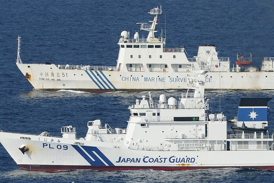 A Japanese coast guard vessel (front) giving chase to a Chinese ship.