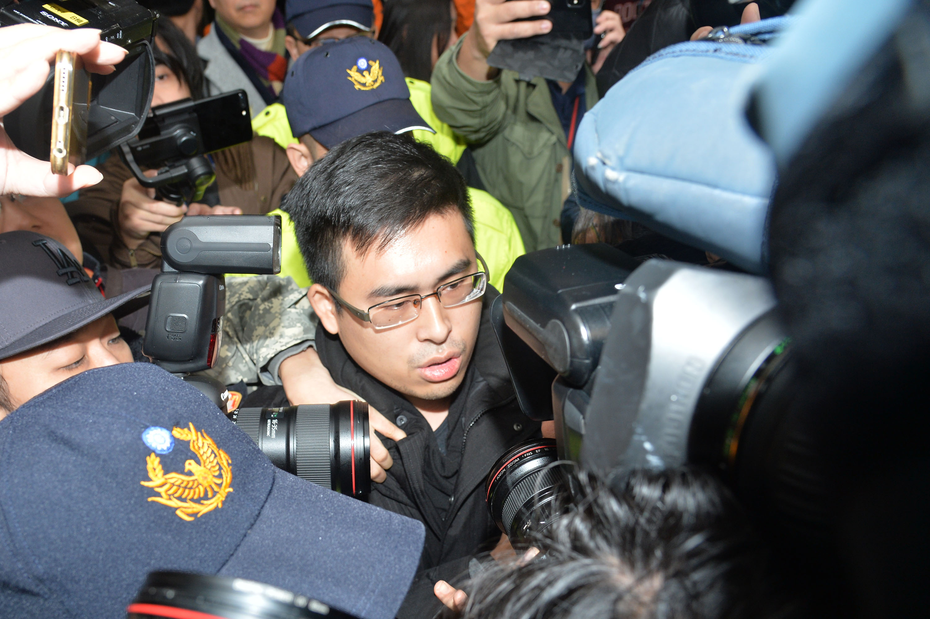 New Party official Wang Ping-chung being taken in for questioning Tuesday.