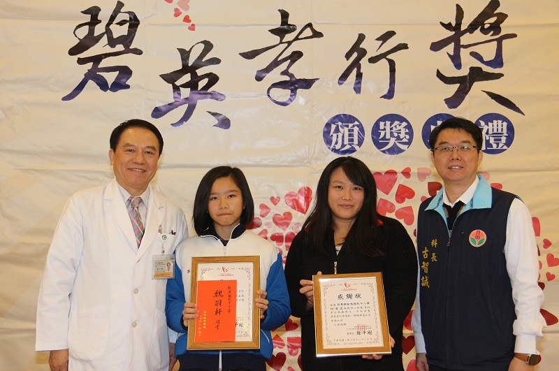 Wei Yu-xuan (魏羽軒) (second from left) receives thefilial piety award with tears welling up in her eyes
