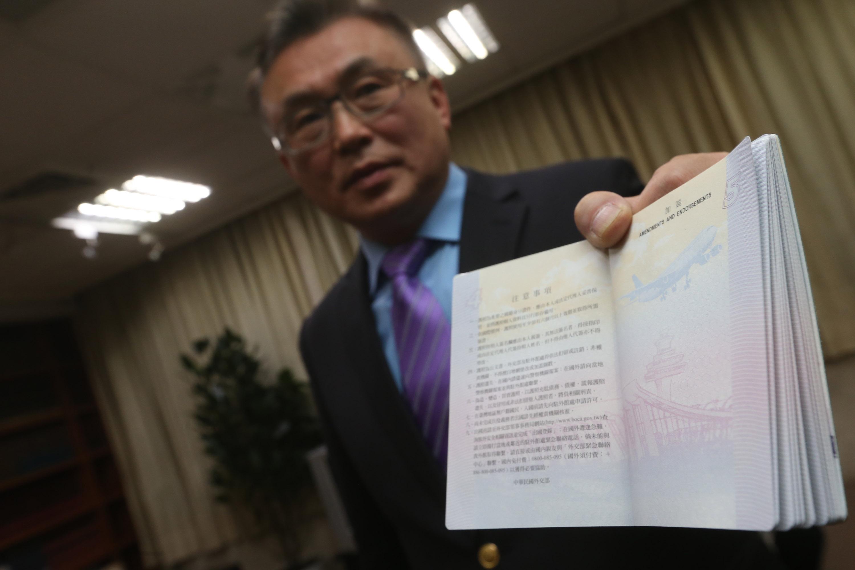 領事事務局護照行政組組長王北平展示被質疑誤用圖案的護照內頁。中央社記者吳家昇攝 106年12月26日