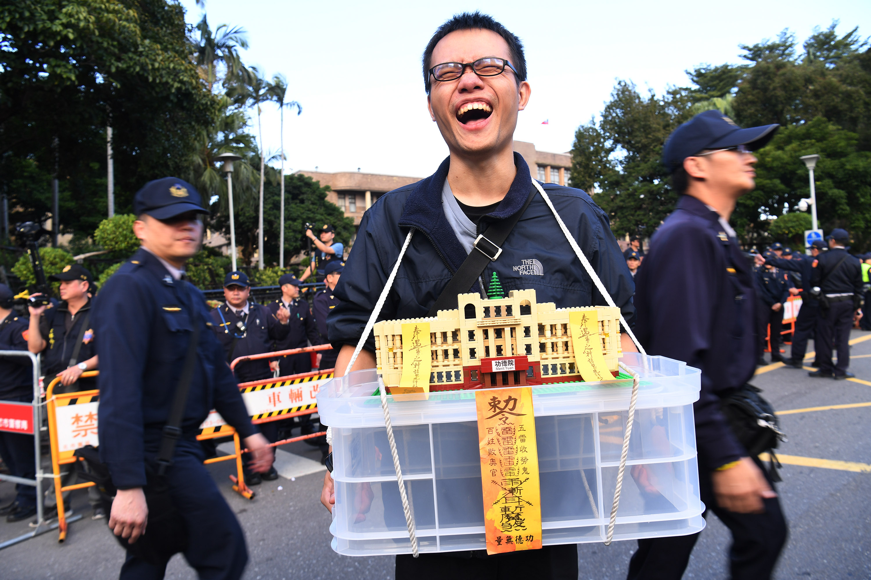 2017年12月26日下午,勞團在台北發起遊行動活動,一名參與活動的民眾展示手作「功德院」模型。
