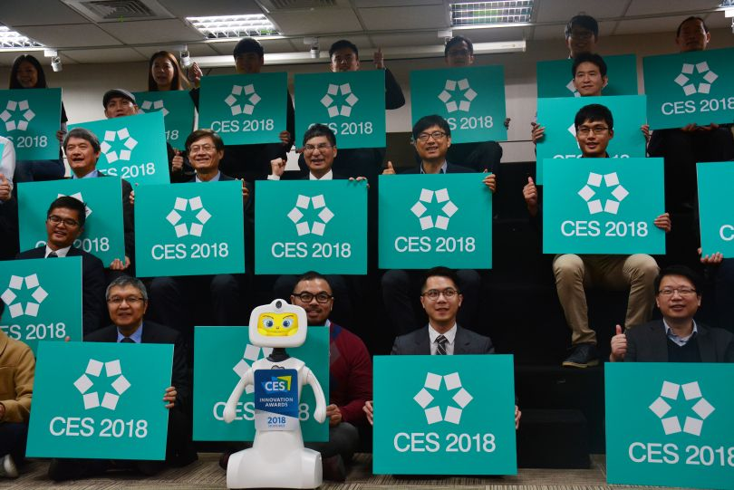 MOST Minister Chen Liang-gee (middle row, third right) holds up a CES placard alongside representatives of local startups in the ministry's delegation...
