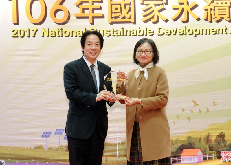 Premier Lai Ching-te (left) presents a trophy at the National Sustainable Development Awards to Huang Yueh-guey, president of Hungkuang University, De