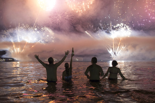 People watch fireworks exploding over Copacabana beach during New Year's celebrations in Rio de Janeiro, Brazil, Monday, Jan. 1, 2018. (AP Photo/Leo C