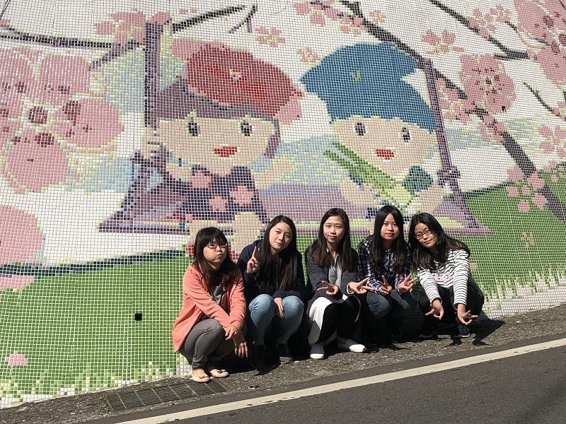 馬賽克磁磚一片片貼上櫻花、稻田、筊白筍等代表三芝的意象娃娃,除了美化牆面,也增添賞櫻情趣。(圖片來源:新北市政府民政局)