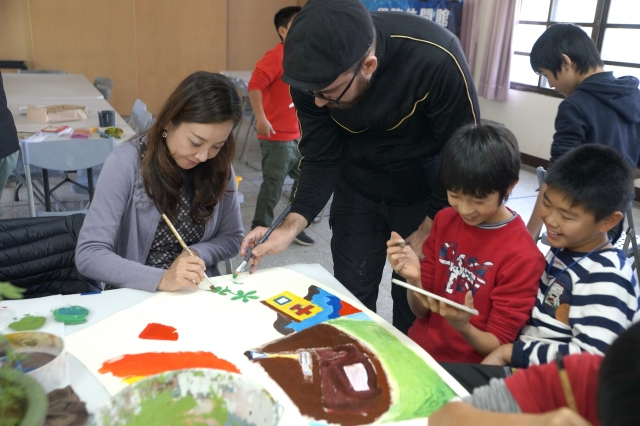 客家事務局長蔣絜安(左)與俄羅斯藝術家林仁亞一同創作魯冰花地景畫作。(桃園客家局)