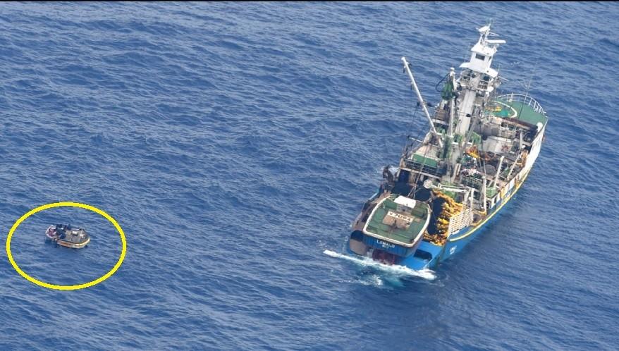 左方小艇(黃圈處) 上的七人,最後被右方的漁船救起。美聯社