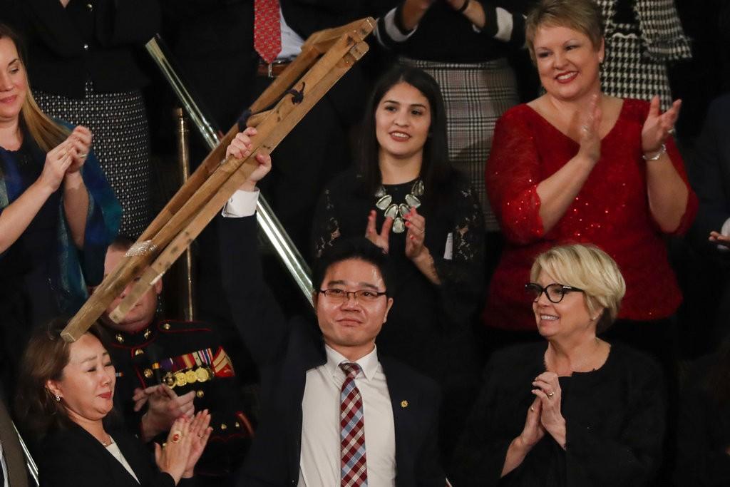 脫北者吉晟浩現身川普演說現場,高舉柺杖接受鼓掌與歡呼聲。(圖片來源:美聯社)