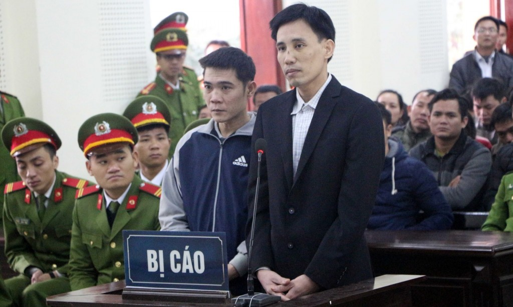 Hoang Duc Binh, center right, and Nguyen Nam Phong, center left, appear in court in the central province of Nghe An, Vietnam, Feb. 6.