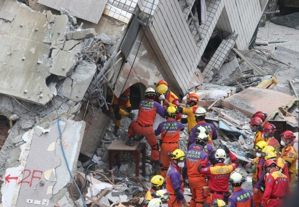 Rescuers remove body from Yun Men Tsui Ti Building.