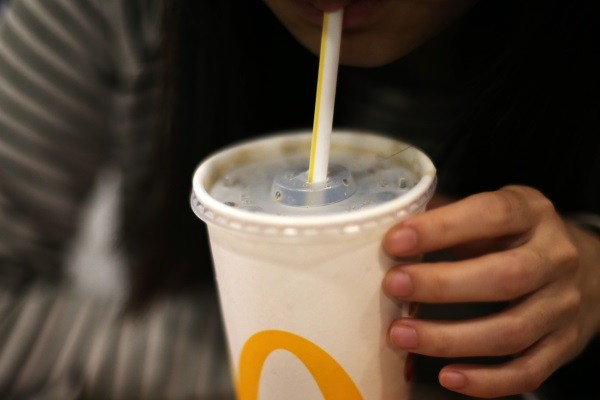 Woman drinking out of a straw at McDonald's.