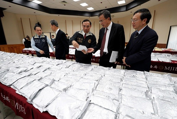 Law enforcement officials with the seized drug shipment.