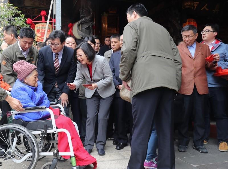 蔡總統(前左4)昨至保安宮,發送總統府特製紅包。台北市長柯文哲(右2)在後方發送保安宮福袋給民眾。立委姚文智(前左3)也向市民拜年。中央社