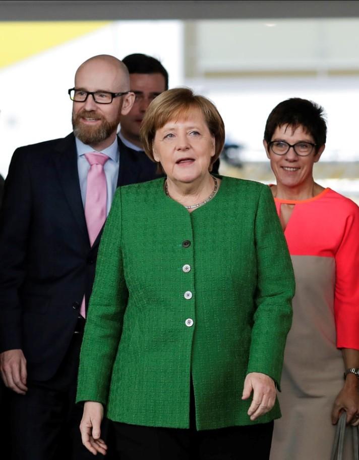 著綠衣者即德國總理梅克爾。美聯社