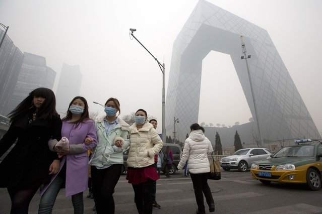 Women wearing masks near China Central Television headquarters.