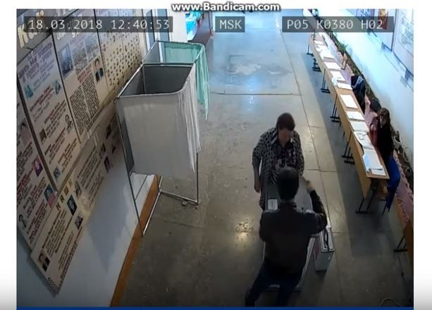 男子正在往投票箱裏塞票(圖片來源:翻攝自YouTube)