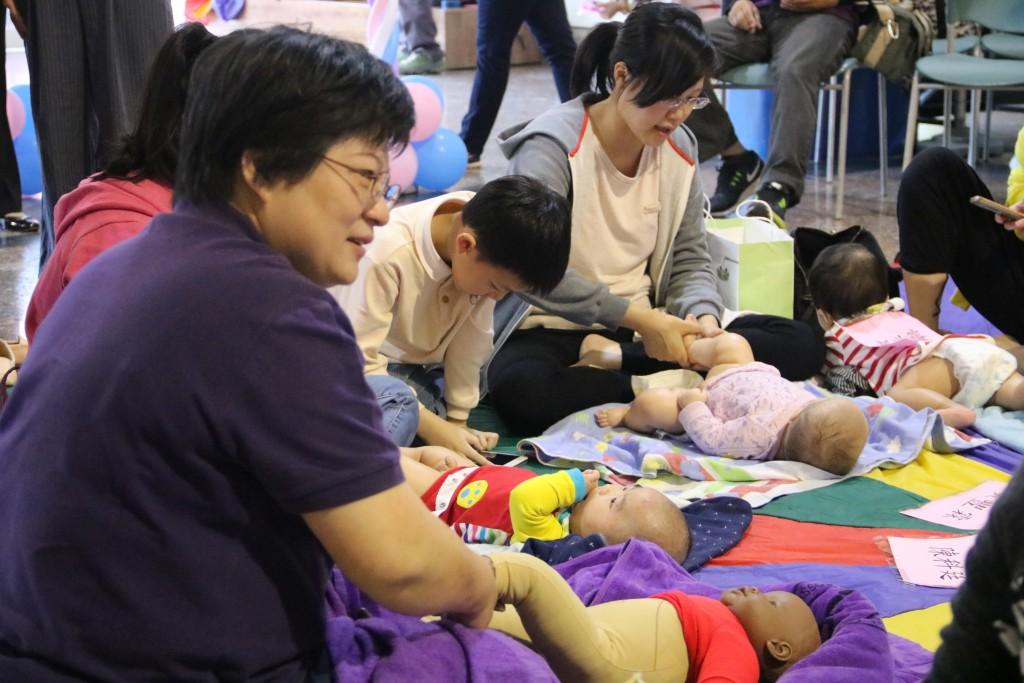 講師(左一)向家長示範教學嬰幼兒按摩。(弘光科技大學提供)