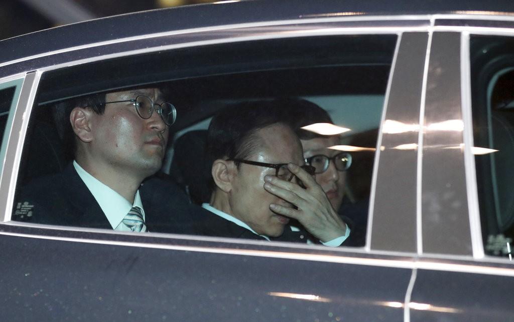 李明博(車中以手遮臉者)在23日前往看守所(圖片來源:美聯社)