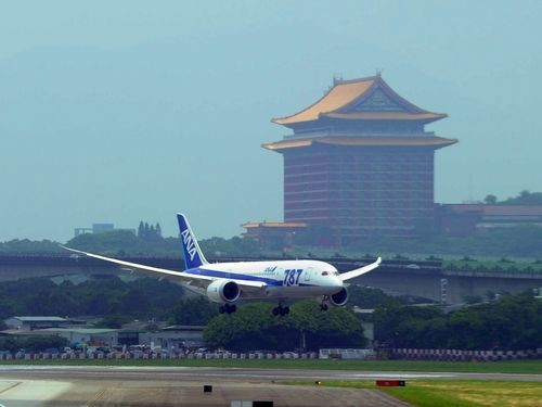Flight landing at Taipei Songshan Airport with the Grand Hotel in the background.