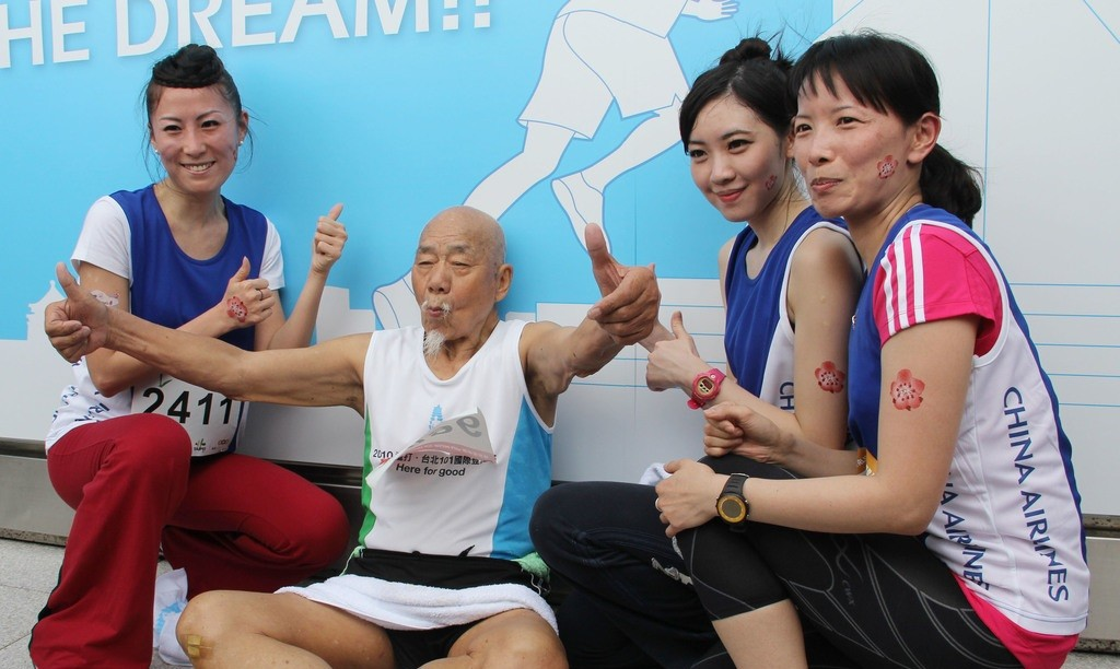 A 96-year-old (2nd from left) takes part in 2013 Taipei 101 Run up. Three China Airlines flight attendants who also participate take a photo with him ...