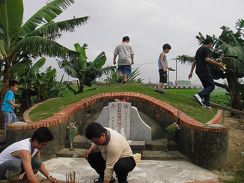 Cleaning the grave of a family member (Image by Flickr user Alec @ Taiwan)